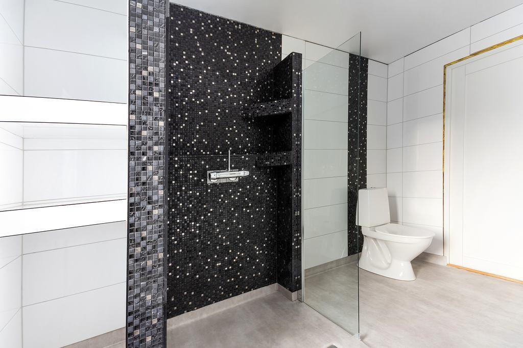 Bakom duschväggen finns platsbyggda hyllor för till exempel handdukar.