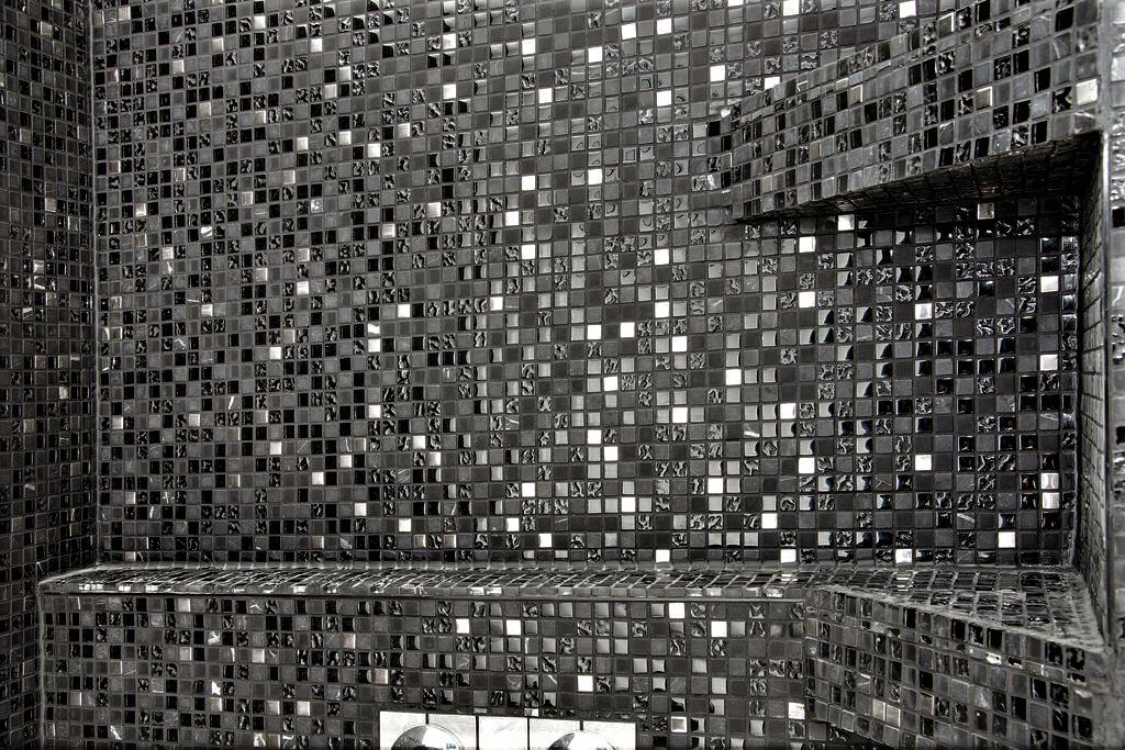 Vacker mosaik och smart hylla för schampo i duschen.