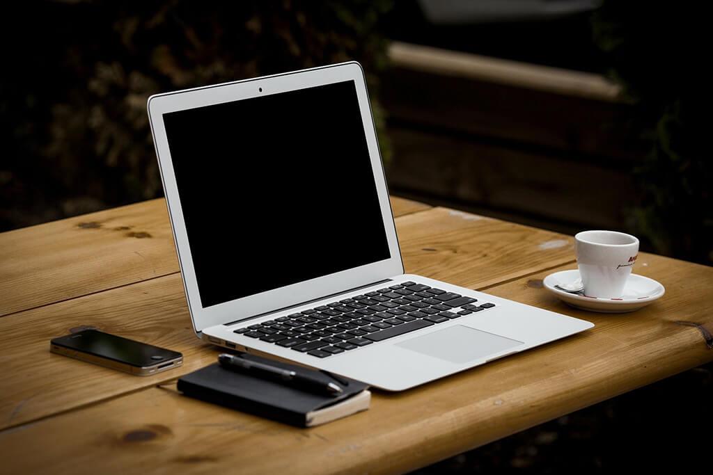 Dator på bord med mobiltelefon och kaffekopp